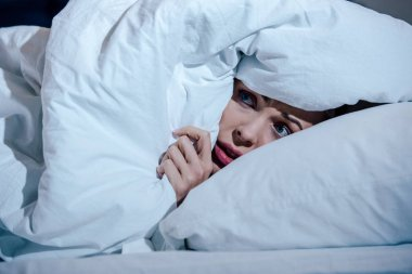 scared woman hiding behind blanket in bedroom at home