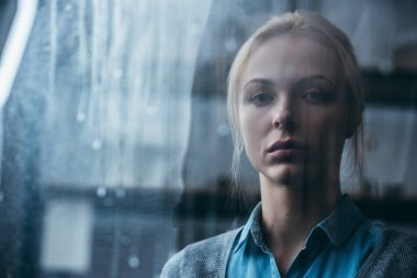selective focus of sad adult woman at home looking at camera through window with raindrops