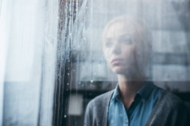 selective focus of sad adult woman at home looking through window with raindrops
