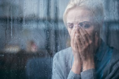 Sad adult woman crying and covering face with hands at home through window with raindrops stock vector