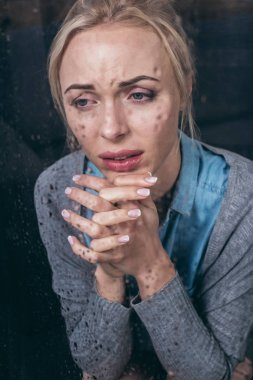 Upset adult woman with folded hands crying at home through window with raindrops stock vector