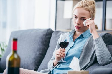 upset woman with glass of wine crying and wiping tears with tissue at home