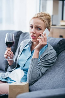 woman sitting on couch, looking at camera, holding glass of red wine and talking on smartphone at home