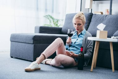 upset woman holding glass of wine and using smartphone at home