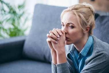 selective focus of upset woman with folded hands sitting at home