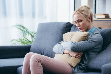 depressed woman sitting on couch and holding pillow at home