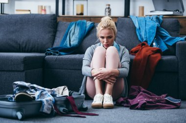 sad woman sitting with scattered clothes and suitcase after breaking up with boyfriend
