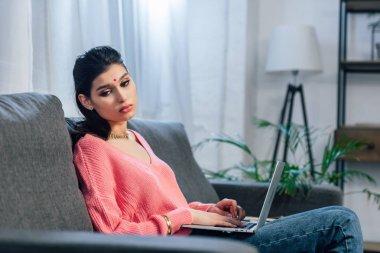 upset indian woman with bindi using laptop on sofa