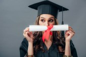 female indian student in graduation hat holding diploma, isolated on grey