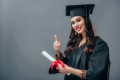 Fotografie smiling female indian student in academic gown and graduation hat holding diploma and showing thumb up, isolated on grey