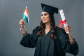 Photo female indian student in academic gown and graduation cap holding diploma and indian flag, isolated on grey