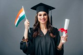 Fotografie happy student in academic gown and graduation cap holding diploma and indian flag, isolated on grey