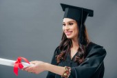 smiling girl in academic gown and graduation hat haking diploma, isolated on grey
