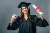 Fotografie happy indian student in academic gown and graduation hat holding diploma, isolated on grey