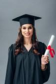 Fotografie usmívající se žena indický student v akademické šaty a oddaný pes drží diplom, izolované Grey