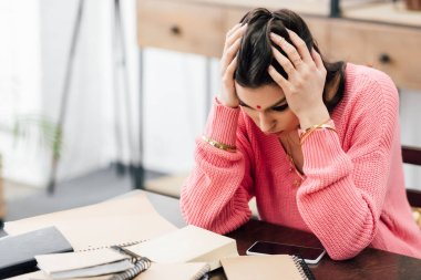 tired indian student with headache looking at notebooks at home