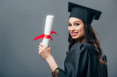smiling female indian student in academic gown and graduation cap holding diploma, isolated on grey