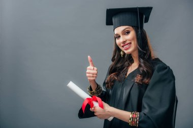 smiling female indian student in academic gown and graduation hat holding diploma and showing thumb up, isolated on grey