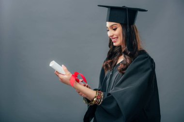happy indian student in academic gown and graduation hat holding diploma, isolated on grey