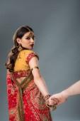 Indisches Paar in traditioneller Kleidung hält die Hände isoliert auf grau