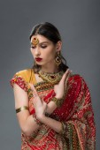 attractive indian woman posing in traditional clothing showing mudra, isolated on grey