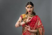 Fotografie attraktive indische Frau in traditioneller Kleidung zeigt Shunya Mudra, isoliert auf grau