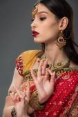 attraktive indische Frau in traditioneller Kleidung, die gyan mudra zeigt, isoliert auf grau