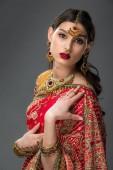 attraktive indische Frau posiert in traditioneller Kleidung und Bindi, isoliert auf grau