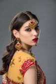 schöne indische Frau posiert in traditionellen Sari und Zubehör, isoliert auf grau