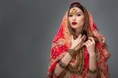 Fotografie attraktive indische Frau posiert in traditionellen Sari und Zubehör, isoliert auf grau