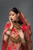 elegante Indianerin in traditionellem Sari und Bindi, isoliert auf grau