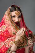 glückliche indische Frau posiert in traditionellen Sari und Zubehör, isoliert auf grau