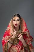 schöne indische Frau posiert im traditionellen Sari, isoliert auf grau