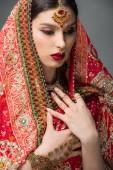Fotografie attraktive Indianerin posiert in traditionellem Sari, isoliert auf grau