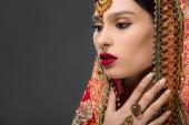 attraktive indische Frau posiert in traditionellen Sari, isoliert auf grau
