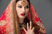 attraktive Indianerin posiert in traditionellem Sari und Accessoires, isoliert auf grau