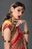 elegante Indianerin posiert in traditionellem Sari und Accessoires, isoliert auf grau
