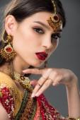schöne indische Frau posiert in traditionellen Zubehör, isoliert auf grau