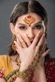schöne indische Frau mit bindi-schließendem Gesicht mit Händen, isoliert auf grau