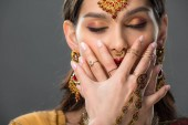 attractive indian woman closing mouth, isolated on grey