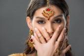 attraktive Indianerin mit Bindi-Gesicht mit Händen, isoliert auf grau