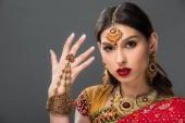 schöne Frau im traditionellen indischen Sari und Zubehör, isoliert auf grau gestikulieren