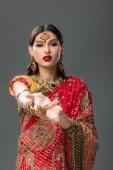 Fotografie elegante Frau gestikuliert in traditionellem indischen Sari und Accessoires, isoliert auf grau