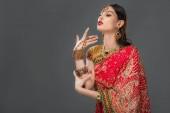 attraktive Inderin Gestikulieren in traditionellen Sari und Zubehör, isoliert auf grau