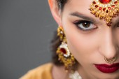 close up of indian woman posing in traditional accessories, isolated on grey