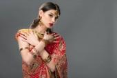 Fotografie indische Mädchen posiert in traditionellen Sari und Zubehör, isoliert auf grau