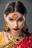 Fotografie attraktive indische Mädchen posiert in traditionellen Sari und Zubehör, isoliert auf grau