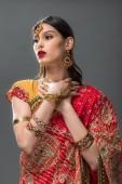schöne Indianerin in Sari und Accessoires, isoliert auf grau