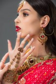 beautiful indian woman gesturing in accessories, isolated on grey