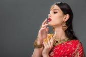 attraktive Inderin Gestikulieren in Zubehör, isoliert auf grau